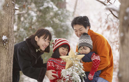 Family with star and snowy tree in forest Stock Photo - 16073660
