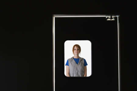 Woman standing behind door window Stock Photo - 16073674