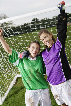 Two friends cheering in front of soccer net Stock Photo - 16073695