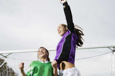low spirited: Two girls cheering in front of soccer net