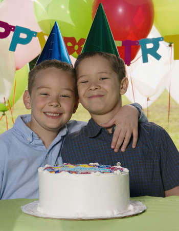 Portrait of two boys hugging with cake at birthday party Stock Photo - 16073697