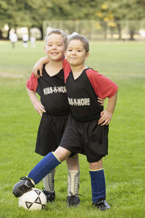 gaiety: Portrait of two boys on soccer field with ball LANG_EVOIMAGES
