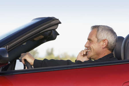 acknowledging: Mature man on cell phone while driving convertable