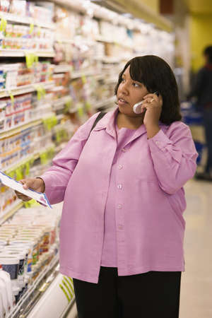 acknowledging: Woman on cell phone with grocery list in store