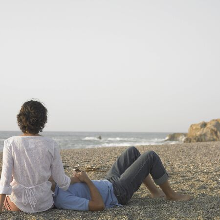 adoring: Young couple relaxing on beach