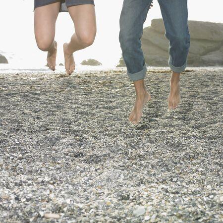 lower section view: Couple jumping for joy on beach