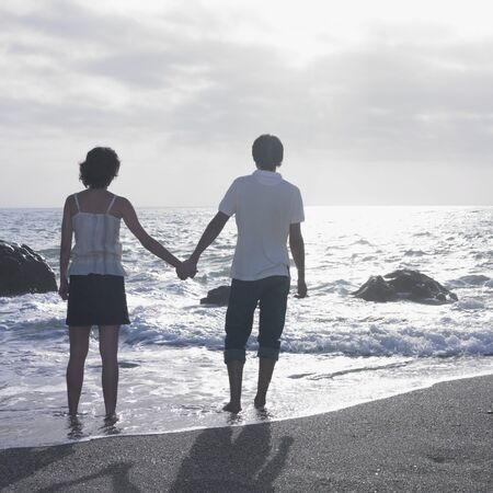 Young couple standing in water on beach Banco de Imagens