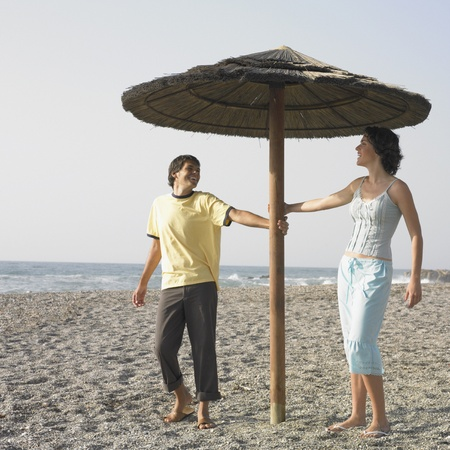 Young couple laughing underneath umbrella on beach Stock Photo - 16073732