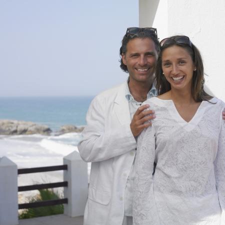 Couple posing on balcony near ocean