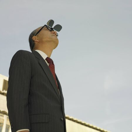 spectating: Low angle view of businessman looking at sky with sunglasses
