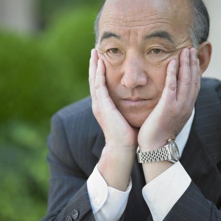 Senior Asian businessman in thinking pose