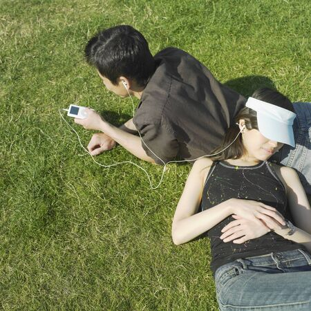 snoozing: Young couple relaxing in grass LANG_EVOIMAGES
