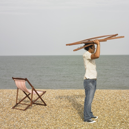 carrying: Young man with lounge chair above his head at beach