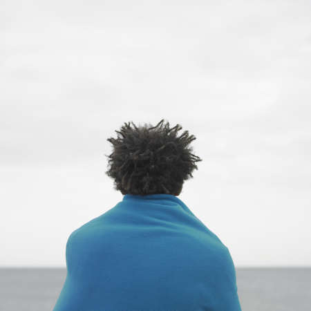spectating: Young man wrapped in blanket looking at ocean