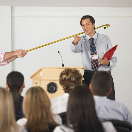 lecturing: Businessman being pulled away from front of crowd
