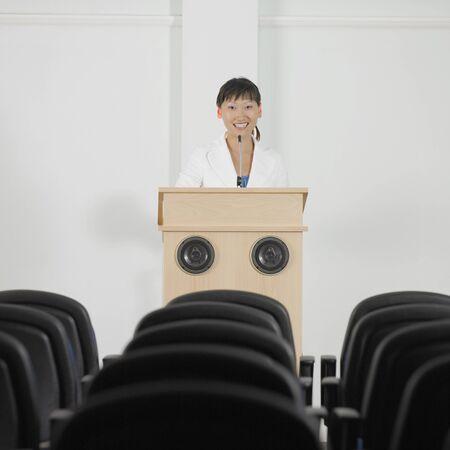 speaker: Businesswoman standing at podium LANG_EVOIMAGES