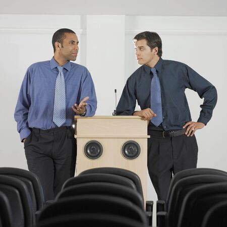 lecturing: Two businessmen leaning on podium