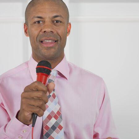 speaker: Businessman speaking into microphone LANG_EVOIMAGES