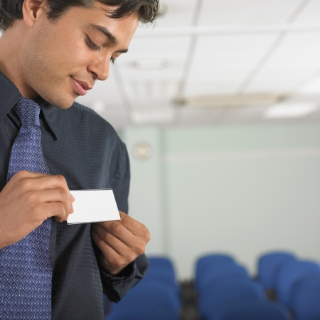Businessman attaching name tag to jacket Stock Photo