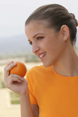 hardy: Young woman smiling with orange in her hand LANG_EVOIMAGES