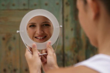 rear view mirror: Young woman looking at herself in mirror LANG_EVOIMAGES