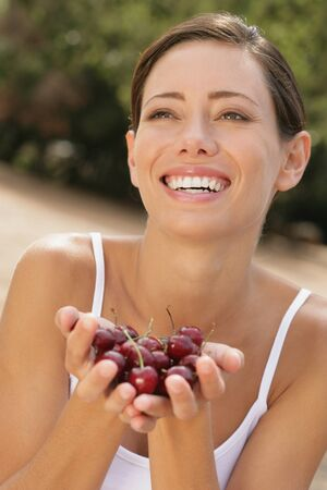 casualness: Young woman smiling with hands full of cherries