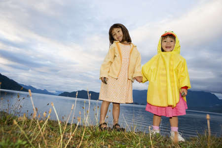 Portrait of sisters holding hands at lake Stock Photo - 16073842