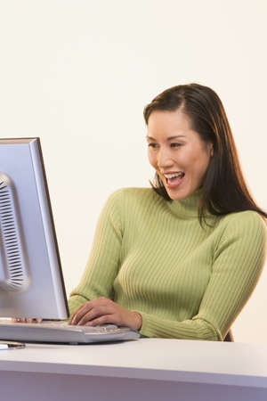 Businesswoman laughing while typing at computer Stock Photo - 16073845