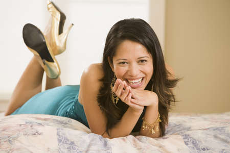 mischievious: Portrait of woman laying on bed smiling