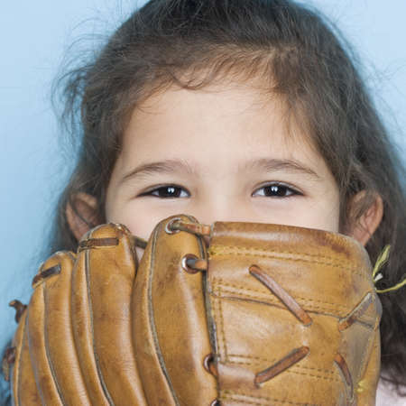 mischievious: Portrait of girl with baseball mitt covering mouth