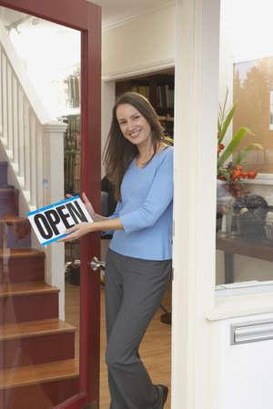 Portrait of woman hanging open sign on shop door Stock Photo - 16073870