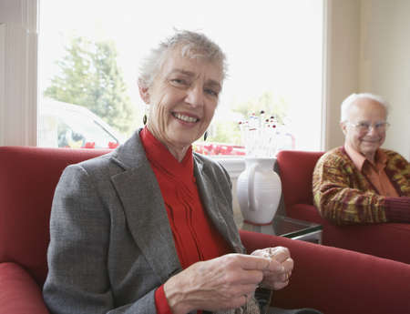 ninety's: Senior woman knitting with husband watching
