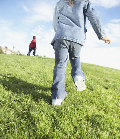 low spirited: Rear view of two children running through grass LANG_EVOIMAGES