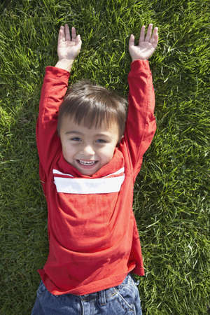 arms above head: Portrait of boy laying on grass with arms above head