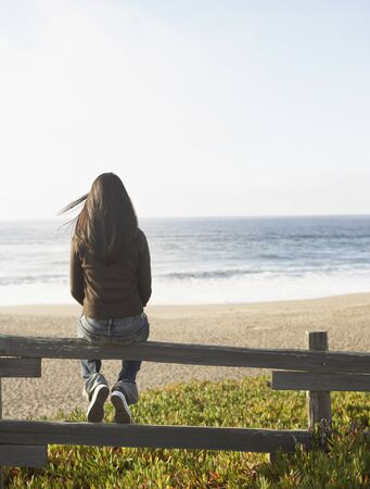 Rear view of woman sitting on fence watching ocean