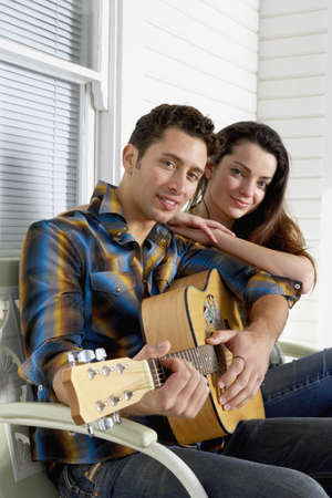 Portrait of young couple with guitar on porch Stock Photo - 16073892