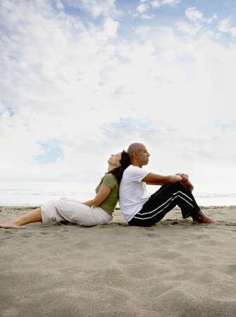 cherishing: Couple sitting back to back at beach LANG_EVOIMAGES