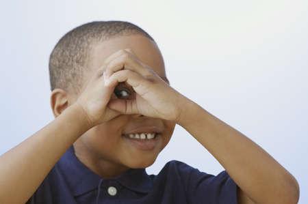 playful behaviour: Close up of African American boy peeking through hands