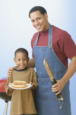 fond of children: Father and young son barbequing hot dogs