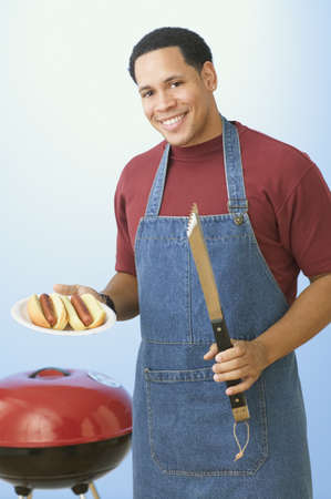 African American man barbequing hot dogs