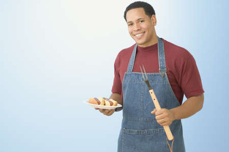 African American man holding hot dogs and barbequing fork
