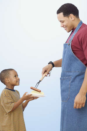 Father giving young son hot dog