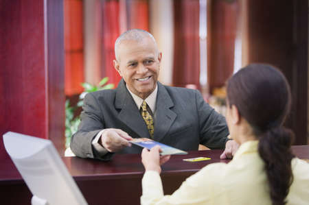 ninetys: Businessman receiving brochure from a receptionist LANG_EVOIMAGES