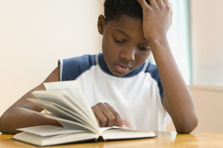 literacy instruction: African American boy reading book LANG_EVOIMAGES