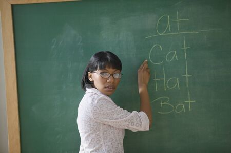 Portrait of female teacher pointing to words on chalk board LANG_EVOIMAGES