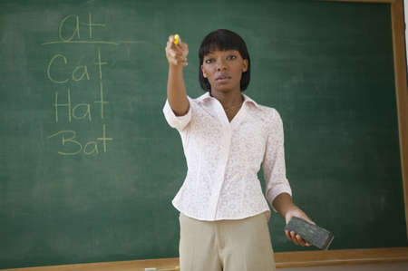 Portrait of female teacher standing by chalkboard and pointing LANG_EVOIMAGES