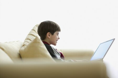 davenport: Side view of boy on couch with laptop