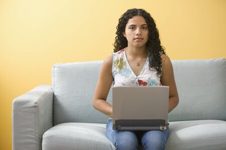 davenport: Portrait of teenage girl sitting on couch with laptop