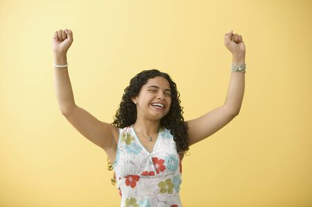 triumphing: Teenage girl cheering with arms raised LANG_EVOIMAGES