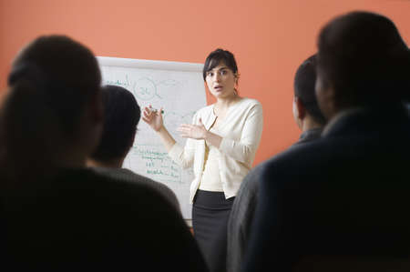 thirty's: Woman giving presentation in meeting LANG_EVOIMAGES
